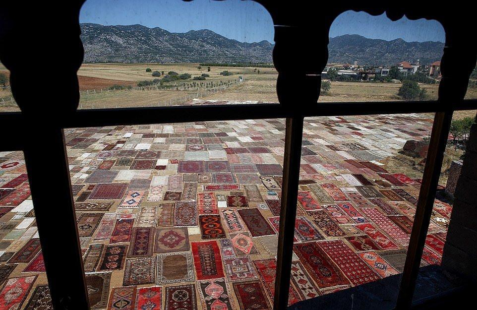 Тысячи ковров ручной работы выгорают под солнцем на поле в Турции